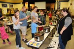People getting samples of chili