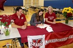 Maeve Donnelly signs papers as parents look on