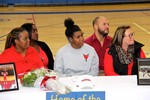 Trinasia kennedy and family at signing table