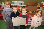 Children pose in front of boxes of donated food