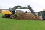backhoe digging up turf