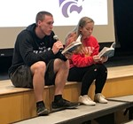 Jarred Freije and Alyssa Lezotte read aloud at student assembly