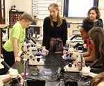 Students and teachers gathered around a microscope during lab experiment.