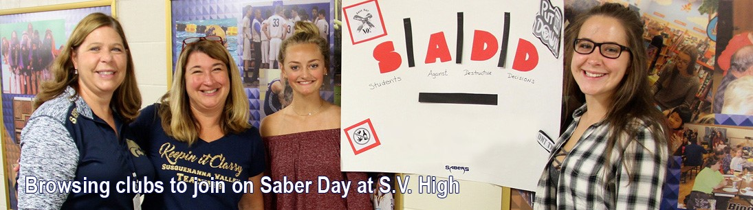 Two teachers and two female students pose before S.A.D.D. poster