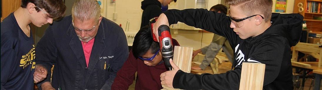 Male teacher and three male students building Adirondack chairs in shop class