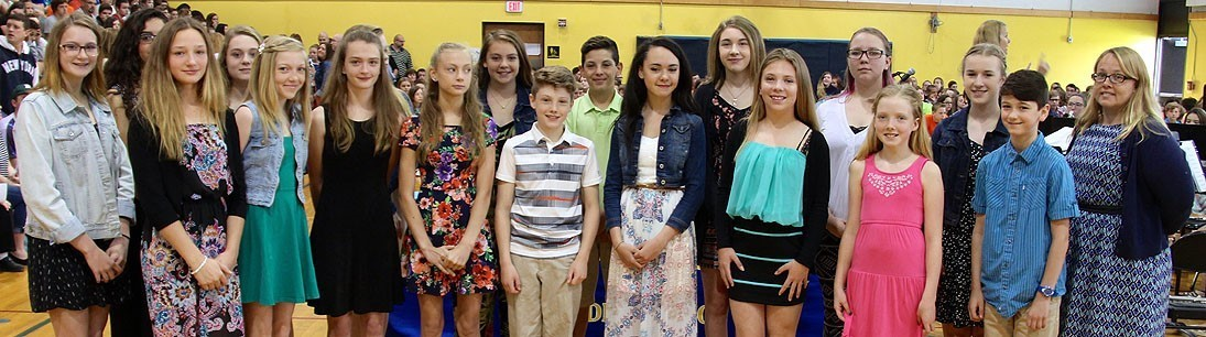 Choir poses for group photo before singing national anthem at awards ceremony at middle school