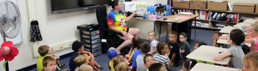 Camp counselor reading to children