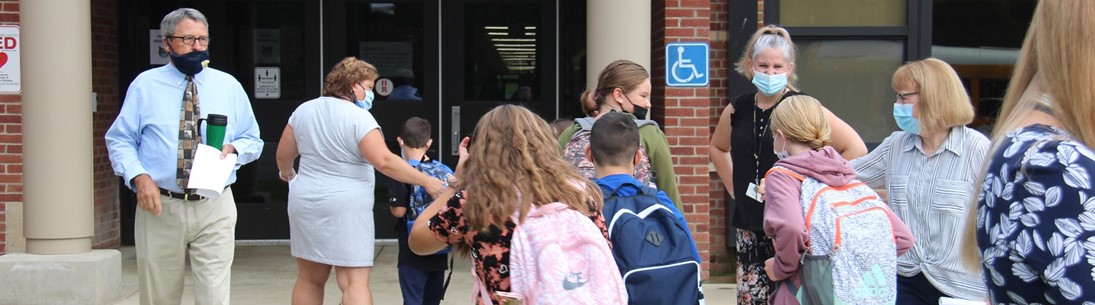 School staff greets students as they walk into Brookside Elementary