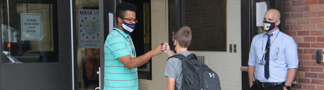 Boys fist bump at entrance to Susquehanna Valley High School