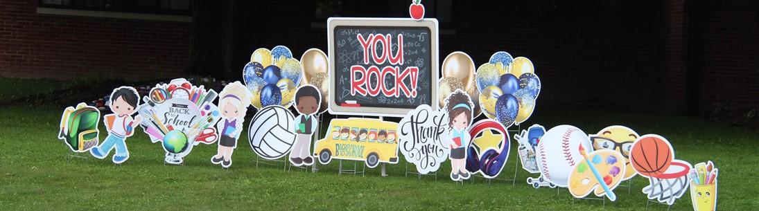 Cardboard lawn display reading You Rock
