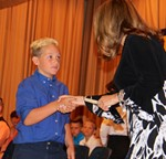 Photo of boy accepting diploma at 5th grade graduation
